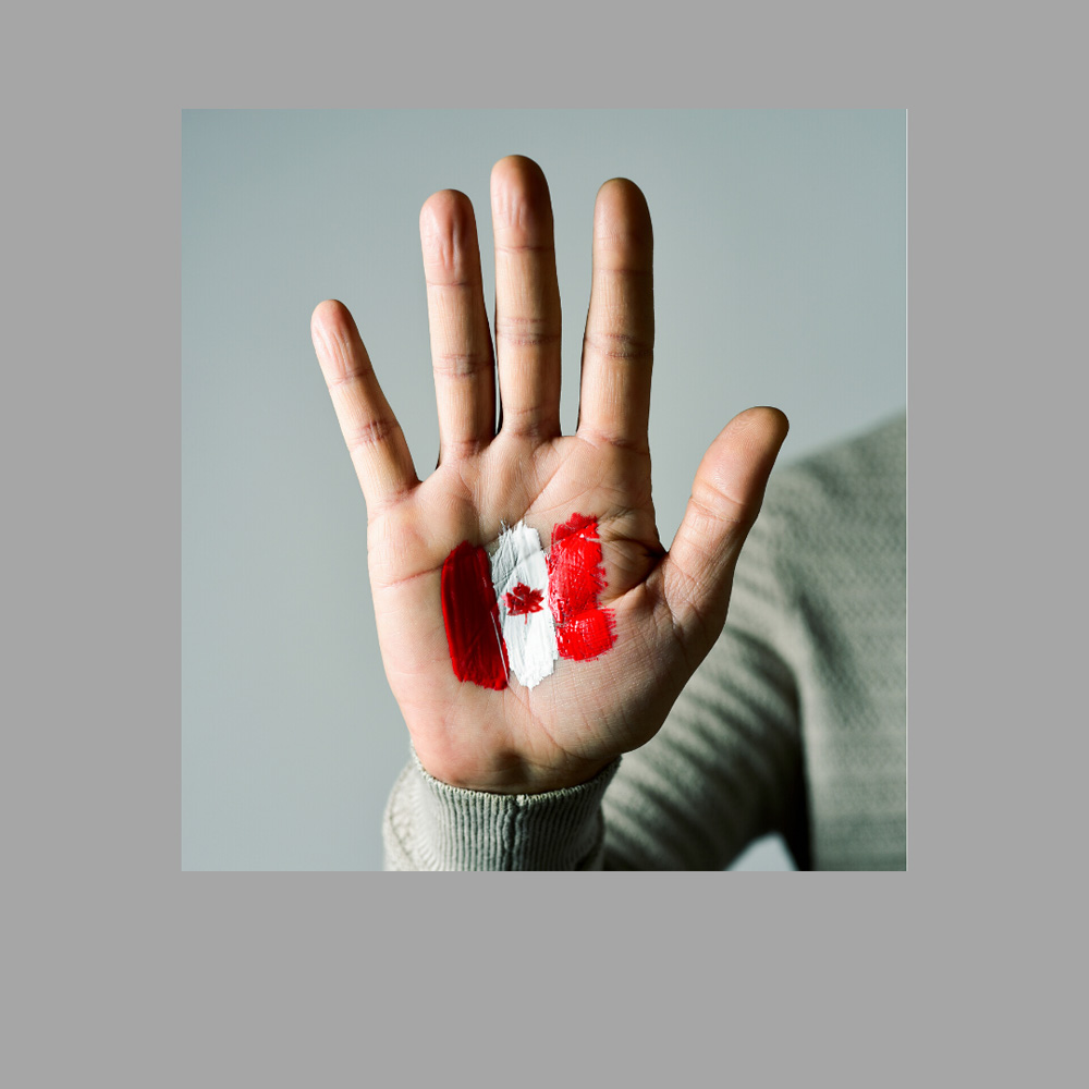 image of a Canadian flag painted on a hand, representative of the immigrant homebuying service provided by Canadian Mortgage Broker Michelle Campbell