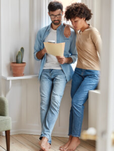 Man & woman reading papers, featured image for Mortgage Insurance and Your Borrowing Power, Michelle Campbell, Canadian Mortgage Broker