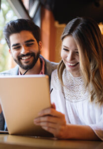Image of a man & woman smiling, reading paperwork, featured image for Mortgage Renewals 101 blog post, Canadian Mortgage Broker Michelle Campbell